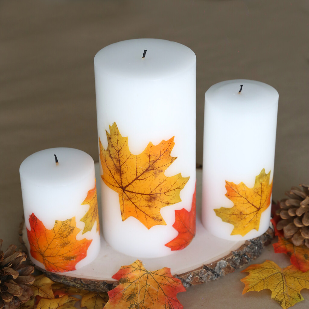 White pillar candles decorated with fall leaves