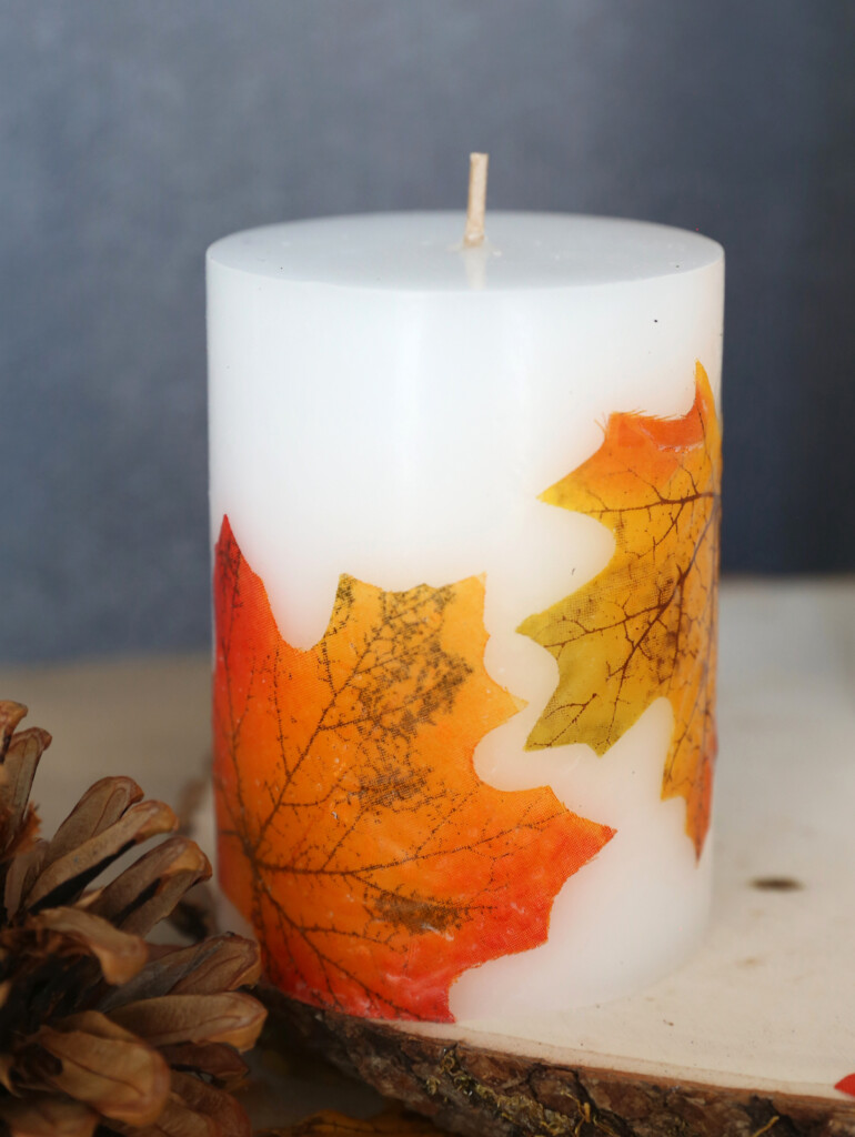 White pillar candle decorated with fall leaves