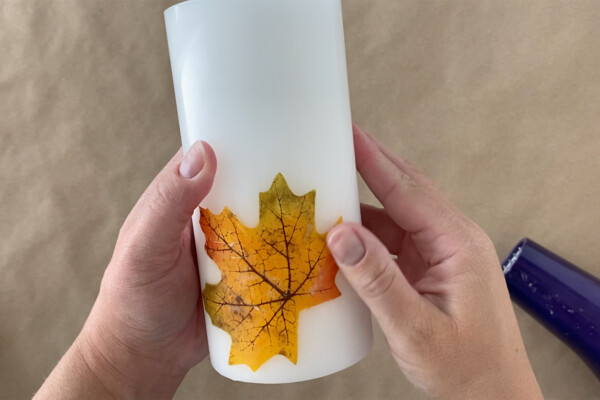 Hand rubbing excess wax off leaf on candle