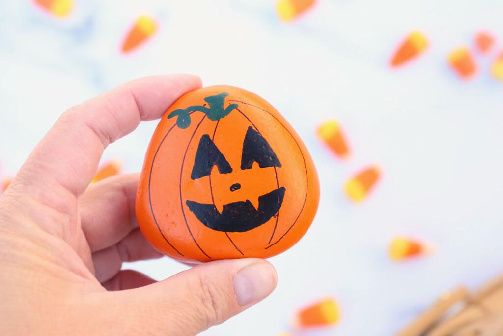 Hand holding a pumpkin painted rock