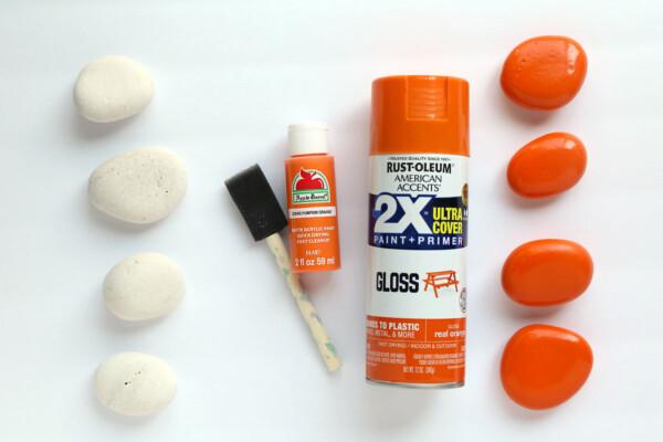 White rocks; paintbrush and orange paint; orange rocks
