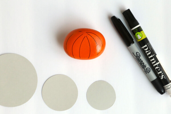 Rock painted orange with card stock circle templates and paint pens