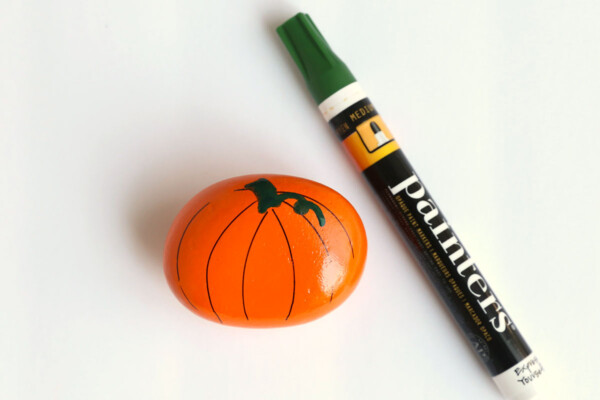 Rock painted orange with stem drawn and green paint pen