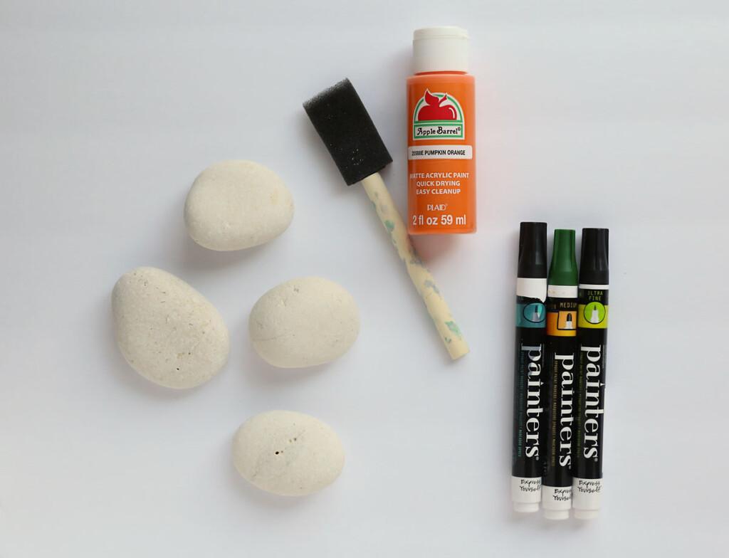 White rocks, foam paintbrush, orange paint, paint pens