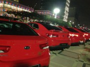 Red is next to white more numbers of cars at the gathering