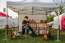"""Rotten Roger"" Pfalzfraf, one of many vendors at the festival, shows off his cigar box guitars made from found objects, like gasoline cans and even bedpans. 