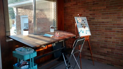 A large desk sits in front of a window, an easel holds an unfinished painting.