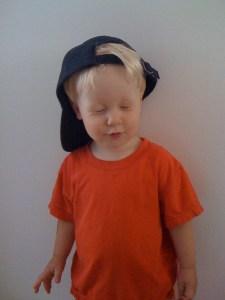 E in backwards baseball cap and silly face