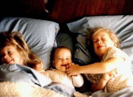 three sisters in a bed