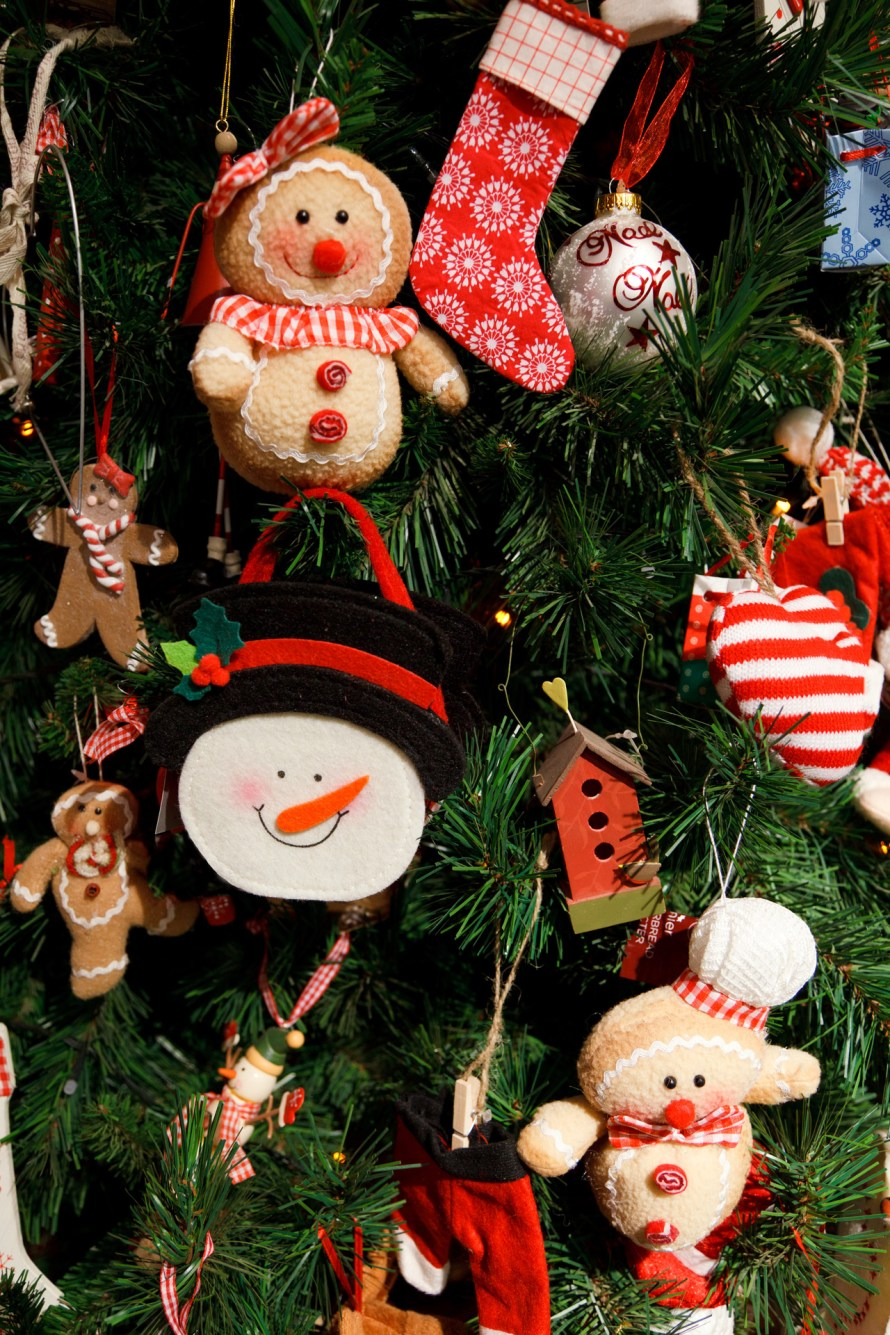 Ornaments on Christmas tree including snowman, gingerbread, red birdhouse & more