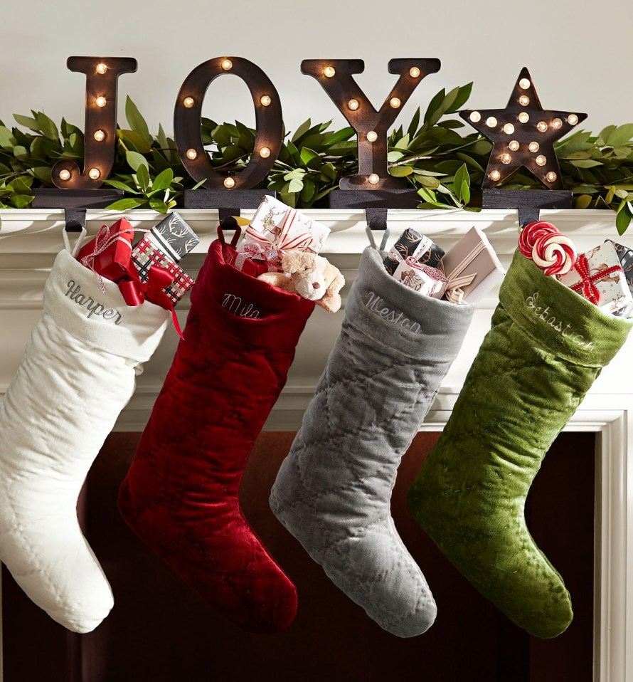 Christmas Stockings, red, white, silver & green hanging at fireplace mantle from holders spelling JOY
