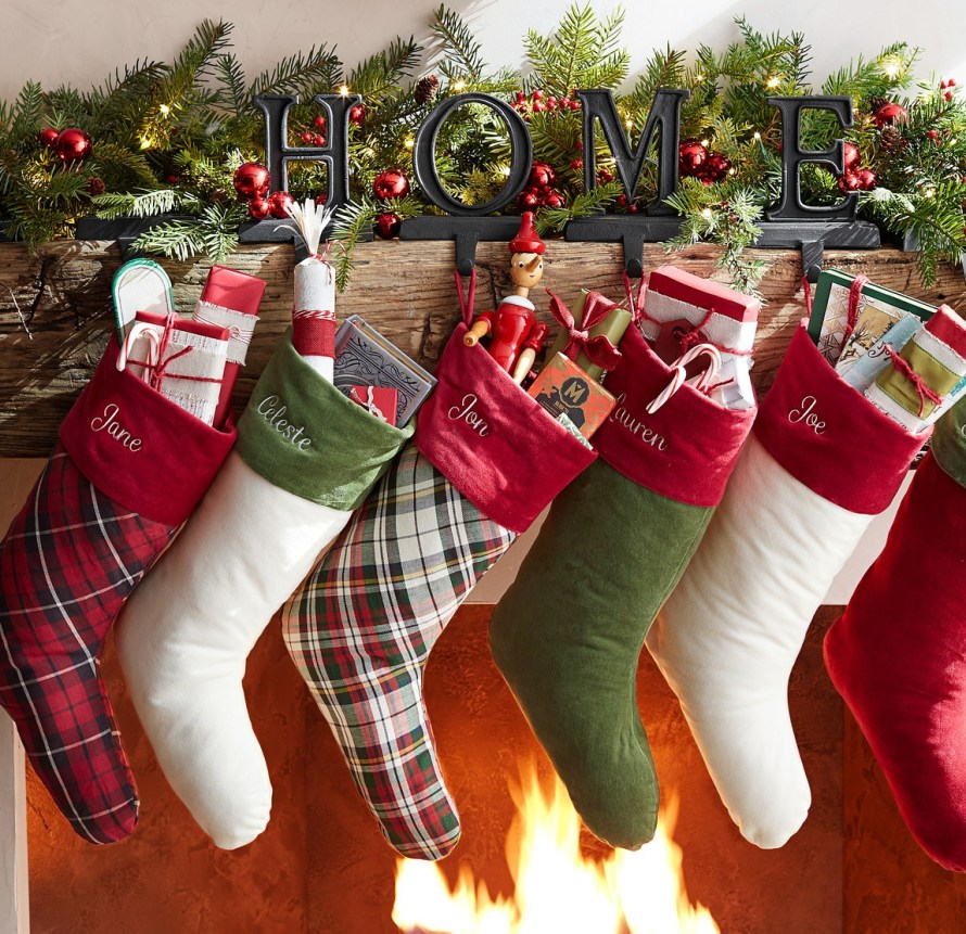 Christmas Stockings, velvet, red, white, & plaid hanging at fireplace mantle from holders spelling HOME