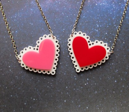 pink and red hear necklaces side by side on space background