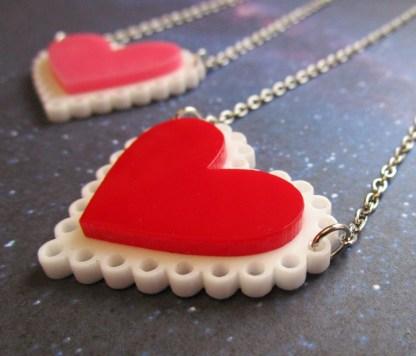 up close view of red heart on white doily layered acrylic pendant necklace with blurry pink version in distance