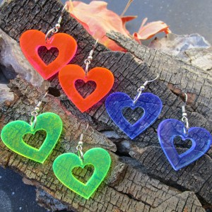 pink blue and neon green heart earrings on wood background