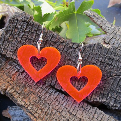 neon pink heart silhouette 80s 90s rave earrings on wood