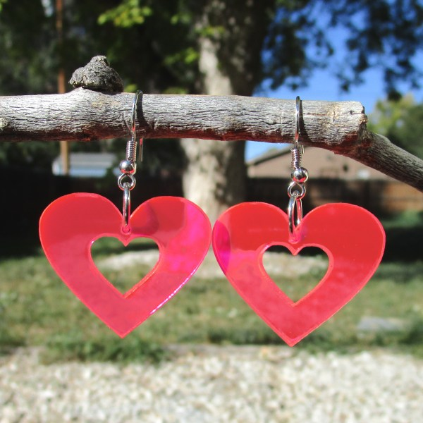 dark pink heart shaped dangle earrings hanging on stick to show transparency