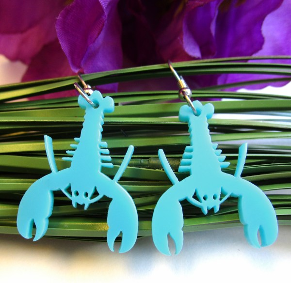 close up of blue teal lobster earrings on grass and purple flower background