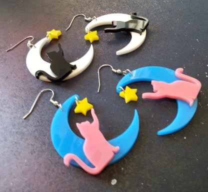 sideways zoom in of Cat on moon with star pendant statement dangle earrings