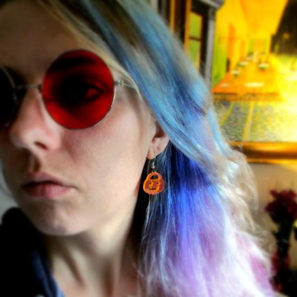 woman wearing red round glasses and orange jack o'lantern dangle earrings