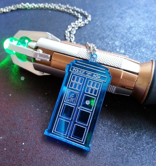 Doctor Who Police box pendant necklace laying on top of sonic screwdriver