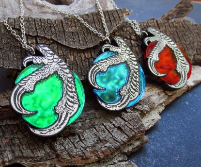 close up of 3 dragon claw and orb necklace pendants with bark background