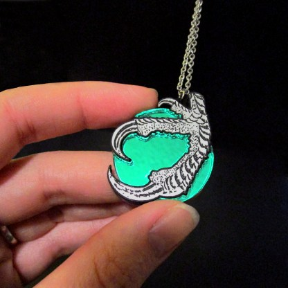 fingers holding green dragon claw and magic ball pendant with black background