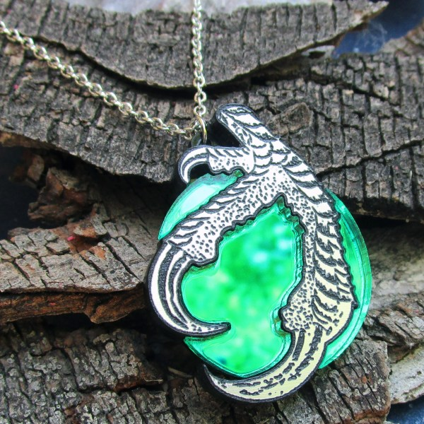 close up of claw and green magic ball pendant with bark background