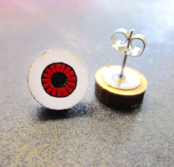 close up of red eyeball earring with earring post pointing up with butterfly clutch