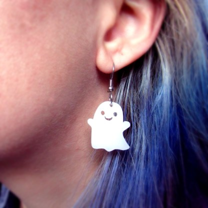 close up of womans ear with happy ghost dangle earring in pierced ear