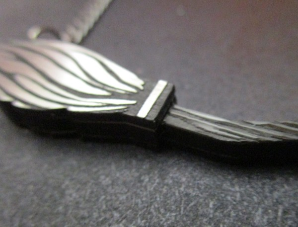 close up of black broomstick pendant necklace where the brush meets the stick