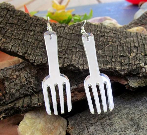 fork shaped pendant earrings on wood background