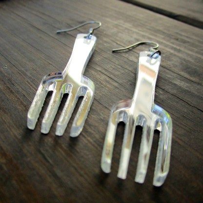 close up picture of fork statement earrings on wood