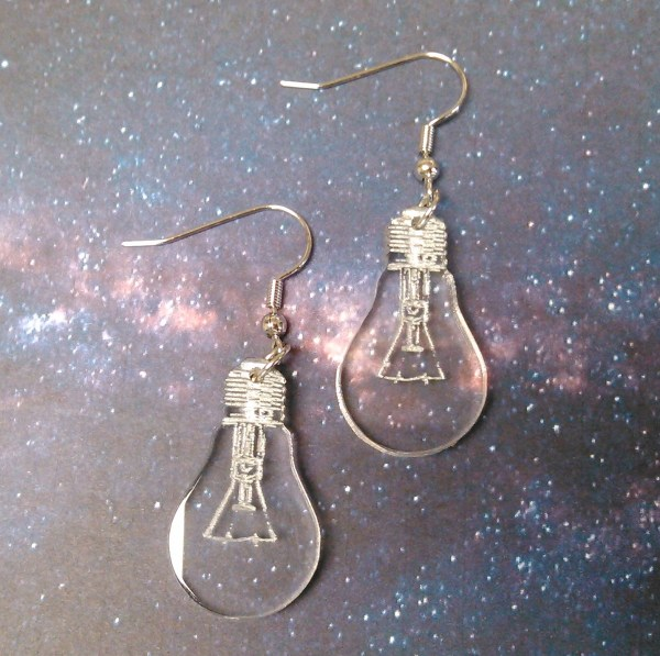 2 lightbult shaped earrings on space background