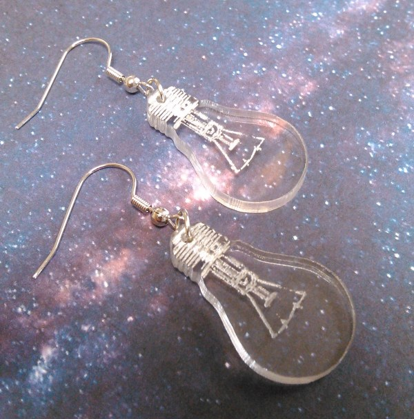 close up of 2 laser cut lightbulb earrings sideways on space background
