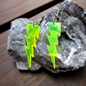 neon yellow lightning bolt earrings on rock