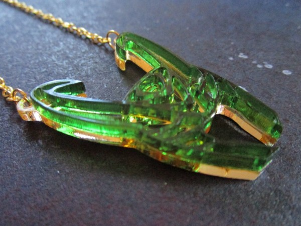 close up of gold and green God of Mischief Loki Helmet Necklace pendant