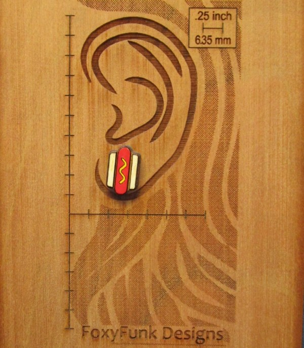 Mini Hot Dog Stud Earring on wood background etched with ear and measurements to show size