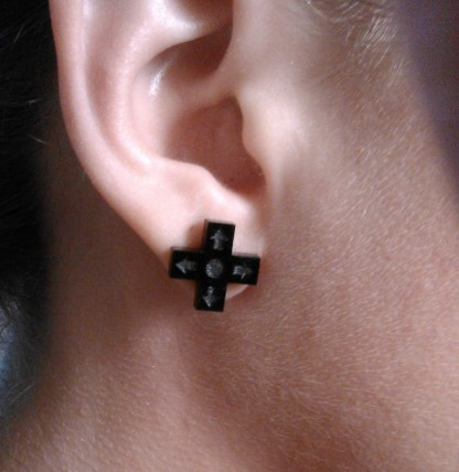 close up of ear with d pad controller button earring