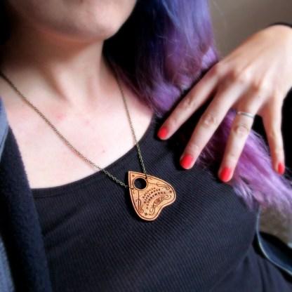 woman wearing ouiji board planchette necklace black shirt purple hair