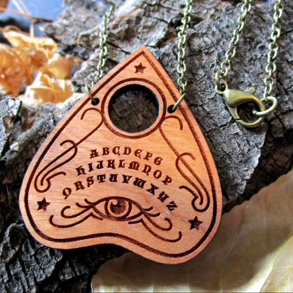 ouiji planchette necklace pendant close up on bark background