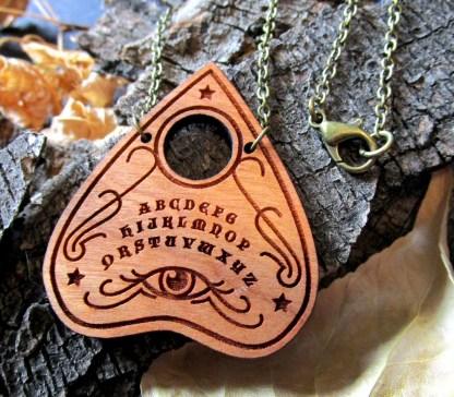ouiji planchette necklace pendant close up on bark background