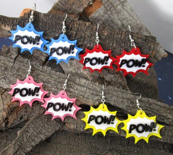collection of colorful acrylic POW! text action comic bubble dangle earrings on wood background