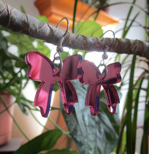 Pink bow earrings hanging off plant with leaves in background