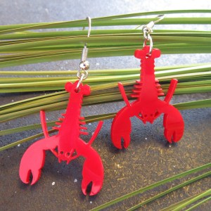 Red Lobster Earrings hanging on grass