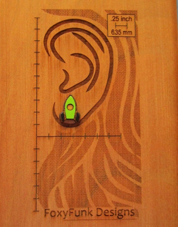 close shot of green rocket ship stud earring that is green on wooden background etched with measurements and ear shape