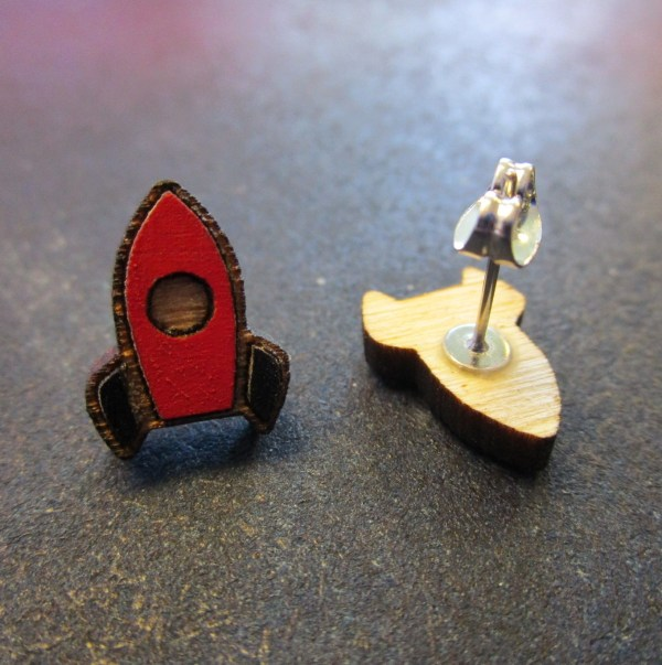close up of red rocket ship stud earrings with one facing forward and one on side to shoe post and clutch back