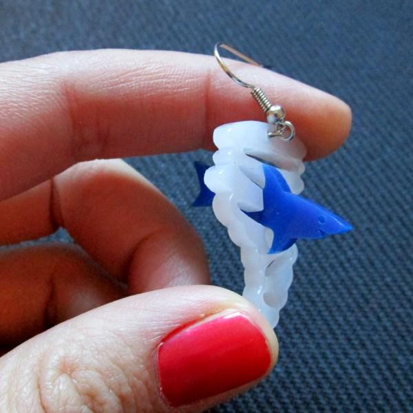 hand holding sharknado pendant earring