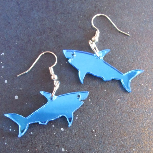 2 blue shark earrings with french earring hooks on space background