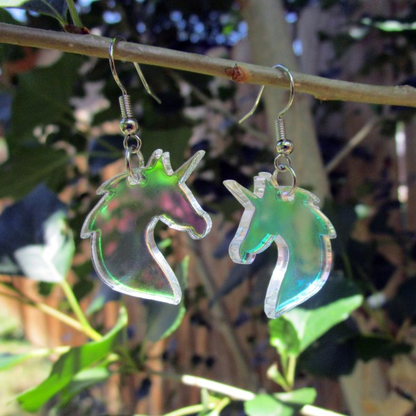 unicorn bust earrings hanging off thin tree branch